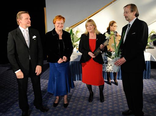 Laatukeskuksen hallituksen puheenjohtaja Tapani Järvinen ja Presidentti Tarja Halonen luovuttavat palkinnon LuontoPortin Eija ja Jouko Lehmuskalliolle.
